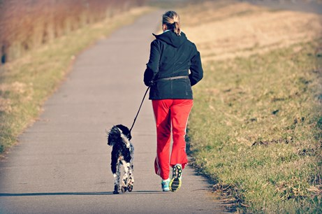 woman jogging with black and white dog on black street through grass in the park in Fayetteville Ark